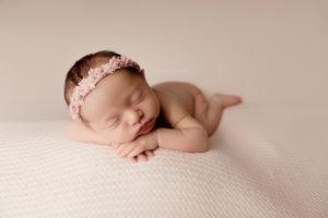 newborn girl sleeping on pink backrop with pink headband